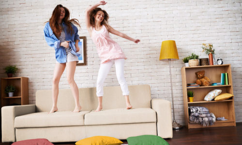 Two friends dancing on sofa